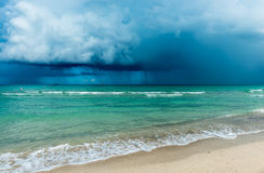Storm over the ocean. USA. Over the ocean storm with heavy clouds, dramatic sky. White sand of  Miami  beach Stock Images