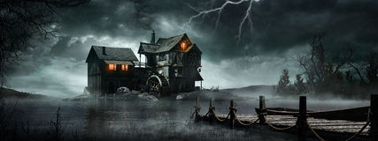 Storm over the old watermill. Night scene with old watermill, stormy sky and foggy lake Stock Photography