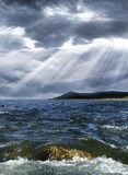 Storm over the sea. Dark clouds pierced by bright sunrays are hanging over the sea Royalty Free Stock Images