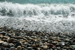Storm på havsstranden av stora kiselstenar arkivfoto