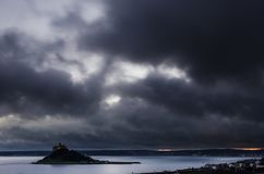 Somber clouds over St Michael`s mount. After a storm passed the dark cloud break up to allow light to illuminate the sea around the iconic landmark St Michael`s Royalty Free Stock Images