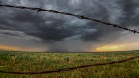 Downpour on the plains through barbed wire fence stock photos