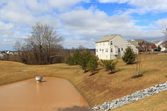 Storm Pond by House. Filled with water after severe thunderstorm and heavy rain at a planned community for drainage, flooding control and management Royalty Free Stock Photography