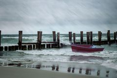 Storm on the sea with a little red boat royalty free stock images