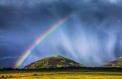 Storm rain shower cloud colourful bright vibrant rainbow over rural landscape Great Britain United Kingdom