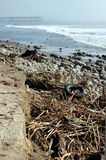Storm-Ravaged Beach. Debris, including a car tire, from a flooded river deposited on a foggy beach near the Ventura Pier in Ventura, California, after big storms Royalty Free Stock Images
