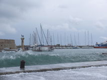 After storm. Rhodes, Mandraki harbor, unsteady sea after the storm, yachts, ship Royalty Free Stock Images