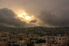 A storm is rising over Bethlehem, Palestine, with the sun breaking briefly through the clouds over the conflict riddled town royalty free stock image