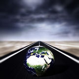 Storm on the road. Road with a thunder storm over it and a globe over it Royalty Free Stock Images