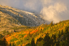 Storm Rolling over the Mountain peaks during the fall season. A storm rolls over the mountain peaks as the trees are turning to red and yellows and gold in the Royalty Free Stock Image