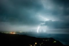 Storm at sea. Lightning strikes several spots on the coast royalty free stock image