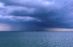 Storm at sea. A sudden storm engulfs a small boat at sea Stock Image