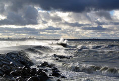 Storm at sea in Tallinn, Estonia. Storm - water waves beat the mole. on the background there is the city silhouette of Tallinns Old Town of Estonia Royalty Free Stock Images