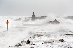 Storm in the sea. With enormous waves invading the levee. A sign of danger notices of the risk Stock Image
