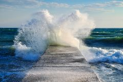 Storm on the sea, a big wave surge. The surge of waves about the pier during a storm at sea royalty free stock images
