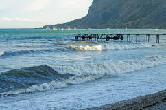Storm on the sea, a mountain range and a small marina. Stock Photo