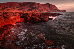 Storm sea at sunset on the mountain coast. In red tone Royalty Free Stock Photos