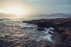 Storm sea at sunset on the south coast. Storm sea at sunset on the mountain coast in cold tone Royalty Free Stock Photography