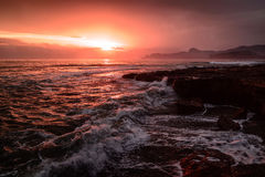 Storm sea at sunset on the south coast. In red tone Royalty Free Stock Photo