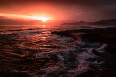 Storm sea at sunset on the south coast. In red toned Royalty Free Stock Photography