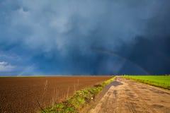 Storm sky and rainbow. Seen above field Stock Photos