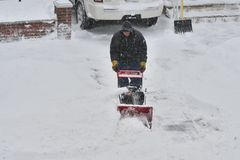 The Storm of snow Juno. A man cleaning up the sidewalk during The Storm of Snow Juno in Middle Village, New York royalty free stock image