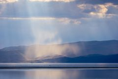 Storm with sunrays over Song Kul lake. Storm with sun rays over beautiful mountains by Song Kul lake, Kyrgyzstan Stock Image