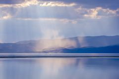 Storm with sunrays over Song Kul lake. Storm with sun rays over beautiful mountains by Song Kul lake, Kyrgyzstan Stock Photo