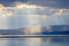 Storm with sunrays over Song Kul lake. Storm with sun rays over beautiful mountains by Song Kul lake, Kyrgyzstan Royalty Free Stock Photography