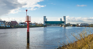Storm surge barrier river Hollandse IJssel. Red radar beacon in the foreground and the lifted Algera flood barrier in the river Hollandse IJssel in the stock images