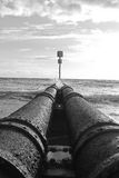 Storm water pipeline at beach. Black and white storm water pipeline feeding into beach with waves crashing over it Royalty Free Stock Image