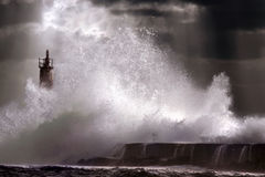 Storm wave. Big storm wave against lighthouse of Vila do Conde, north of Portugal (enhanced sky Royalty Free Stock Images