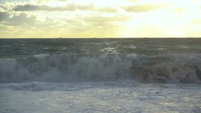 Storm wave swirls on the shore and on the horizon of the ship slow mo stock video footage