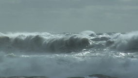 Storm waves breaking against rocks stock footage