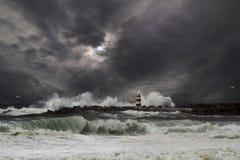 Storm. Waves over beacon of the harbor of Povoa do Varzim, Portugal - enhanced sky Royalty Free Stock Photos