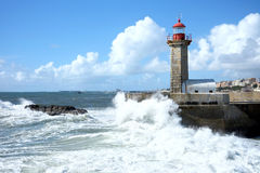 Storm waves over lighthouse in Porto, Portugal. Storm waves over lighthouse and blue sky in Porto, Portugal Royalty Free Stock Photo