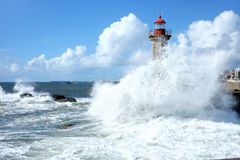 Storm waves over lighthouse in Porto, Portugal. Storm waves over lighthouse and blue sky in Porto, Portugal Stock Images