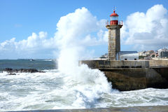 Storm waves over lighthouse in Porto, Portugal. Storm waves over lighthouse and blue sky in Porto, Portugal Royalty Free Stock Photography