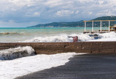Storm waves roll on the breakwater. Stock Photos