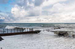 Storm waves roll on the breakwater. Stock Photography