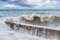 Storm waves roll on the breakwater Stock Photos