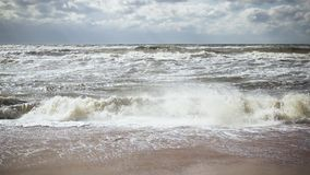 Storm waves in the sea and on the shore slow motion. Storm waves in the sea and on a sandy beach under a sunny sky with white clouds slow motion stock video footage