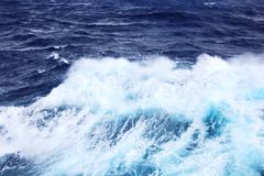 Storm waves in the world ocean. Kind of waves, crests, splashes, foam against the background of the sea and blue sky. Storm waves in the world ocean. Kind of royalty free stock photography