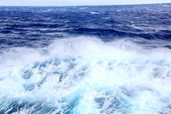 Storm waves in the world ocean. Kind of waves, crests, splashes, foam against the background of the sea and blue sky. Storm waves in the world ocean. Kind of royalty free stock image