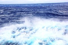 Storm waves in the world ocean. Kind of waves, crests, splashes, foam against the background of the sea and blue sky. Storm waves in the world ocean. Kind of stock photography