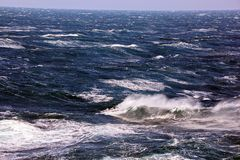 Storm waves in the world ocean. Kind of waves, crests, splashes, foam against the background of the sea and blue sky. Storm waves in the world ocean. Kind of stock images