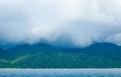 Storm white cloud with rain above island Stock Images