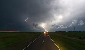 Storma med blixt i natthimlen på vägen arkivfoton