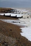 Stormachtig Engels Strand met golfbrekers Stock Foto's