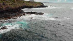 Stormachtig oceaan, wit schuim van de golven die de kustlijn van bevroren vulkanische lava raken Op de achtergrond zijn bergen stock videobeelden